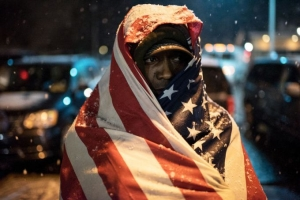 A protester covered in a U.S. flag stands in front of Ferguson Police Department as the snow falls, in Ferguson, Mo. on Nov. 26, 2014.