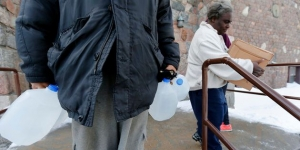 Residents carry free water being distributed at the Lincoln Park United Methodist Church in Flint, Michigan, on Feb. 3, 2015. It wasn't till October that the county declared a public health emergency.