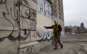 Laborer Brian Kuhn paints over graffiti on a blighted building near downtown Detroit in Detroit, Michigan, December 10, 2014
