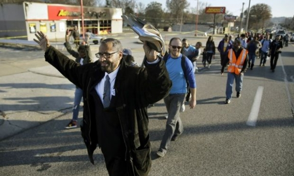 Marchers walk past a burned-out business in Ferguson, Missouri, on their way to Jefferson City.